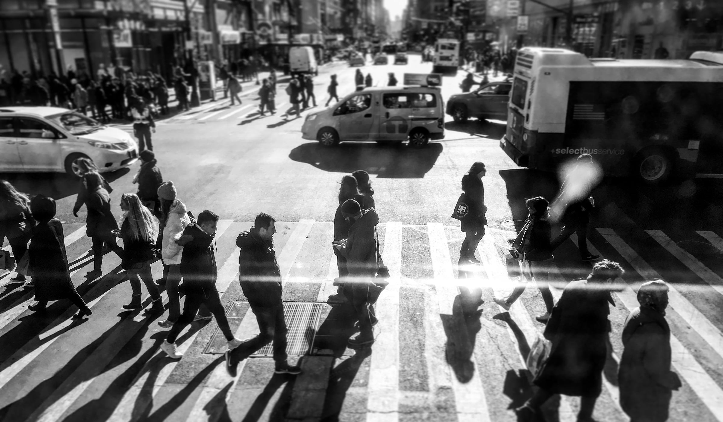 Pedestrians at a busy street crossing in New York City.