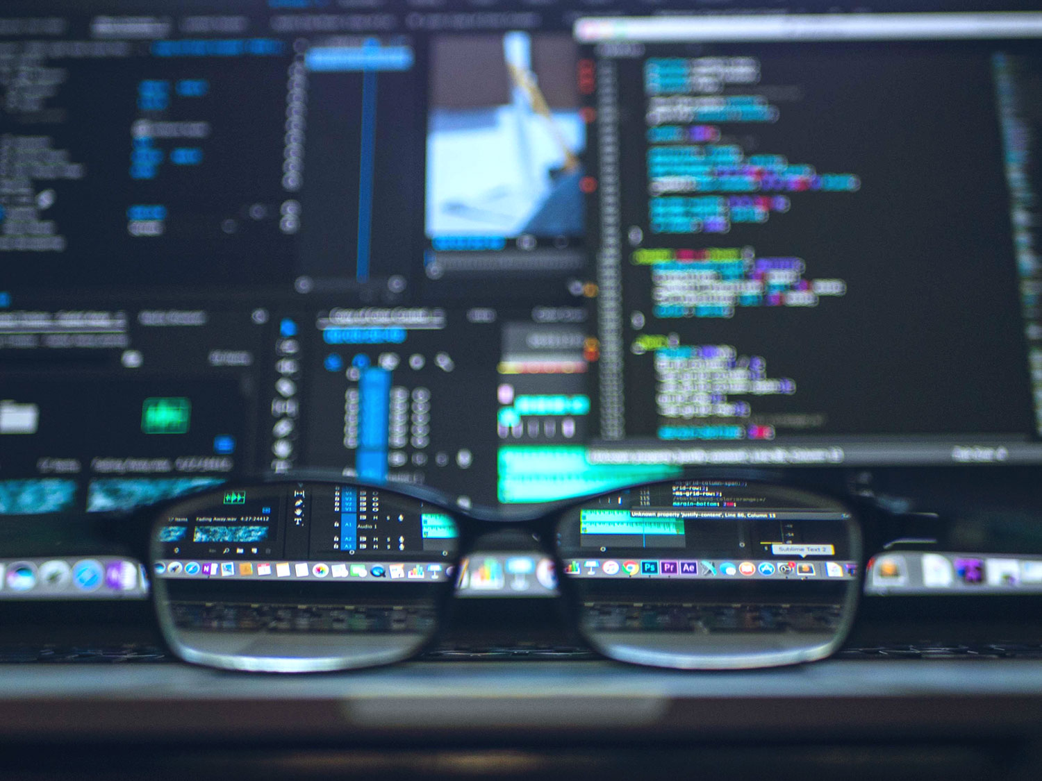 glasses resting on laptop with coding programs on screen