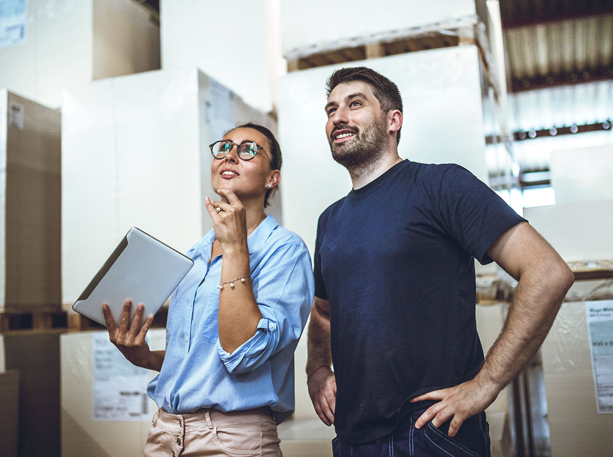 impressed man and woman standing in warehouse in front of powering boxes