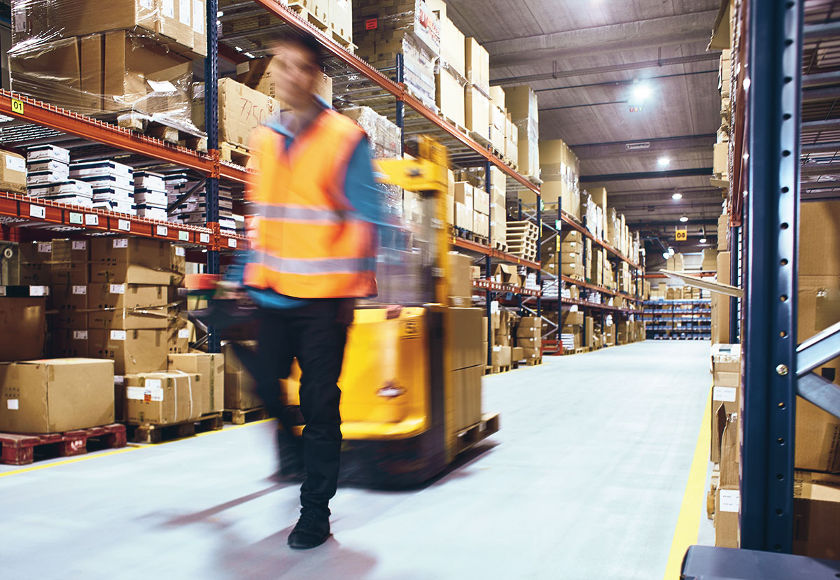 worker moving goods down large warehouse aisle