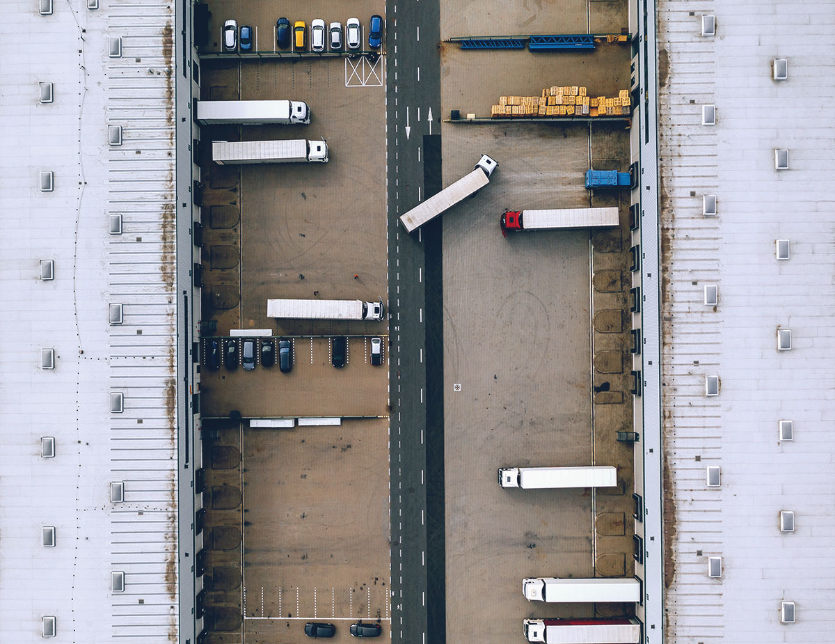 overhead view of large warehouse and parked delivery trucks