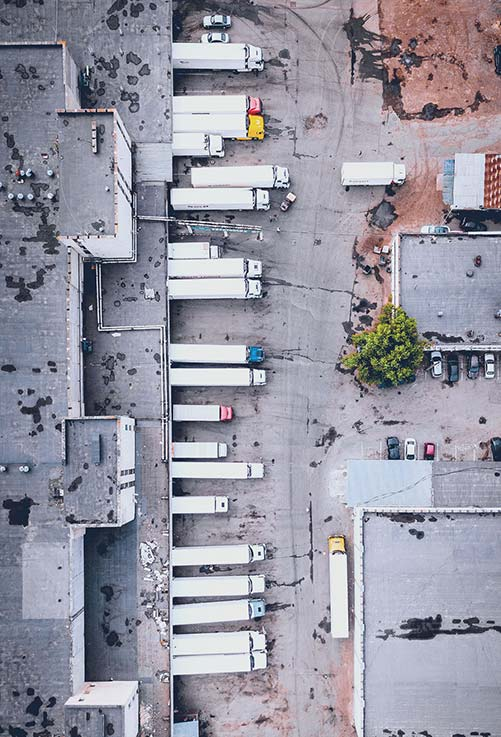 Overhead view of delivery trucks parked at warehouse