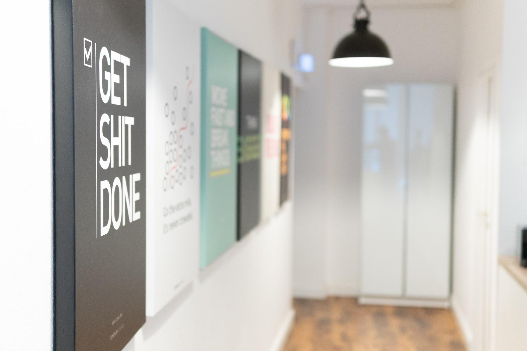 """Mehrere Bilder, die aufgereiht an der Wand hängen. Auf dem ersten Bild steht der Schriftzug """"GET SHIT DONE""""."""