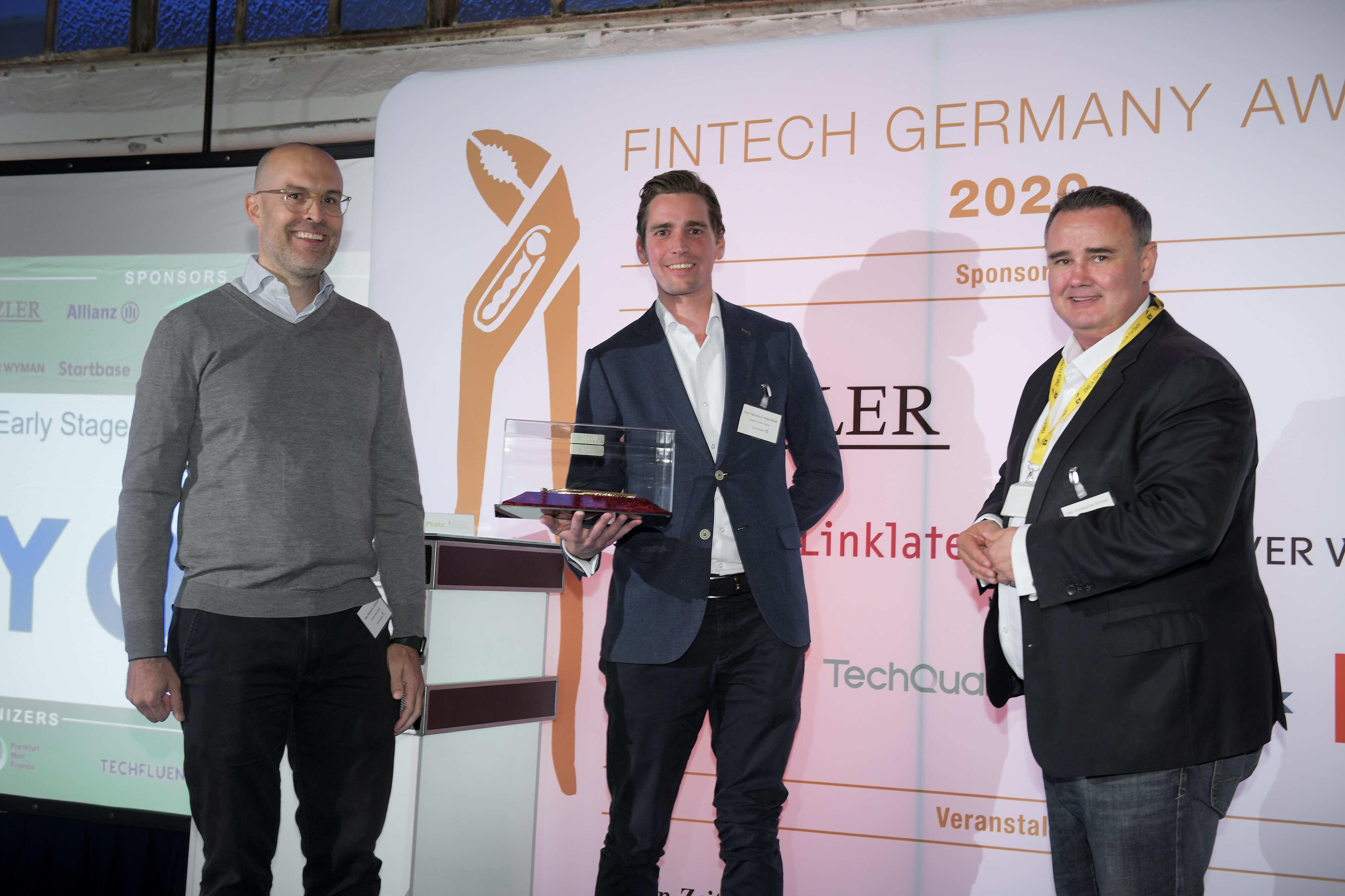 Die beiden Myos Gründer Benjamin Schickert und Nikolaus Hilgenfeldt stehen auf einer Bühne und empfangen den Fintech Germany Award 2020 Preis.