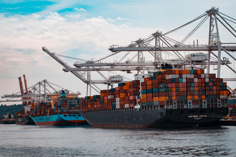Geladene Containerschiffe ankern in einem Hafen. Hafenkräne stehen bereit um Container von den Schiffen abzuladen.