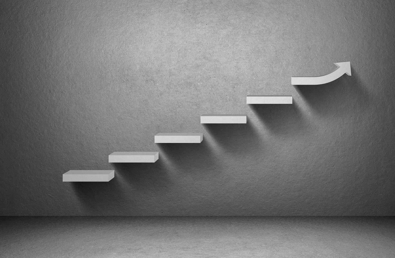 Graue steigende Stufen an einer grauen Wand. Die letzte Stufe ist ein steigender Pfeil. Das Bild zeigt einen Anstieg.