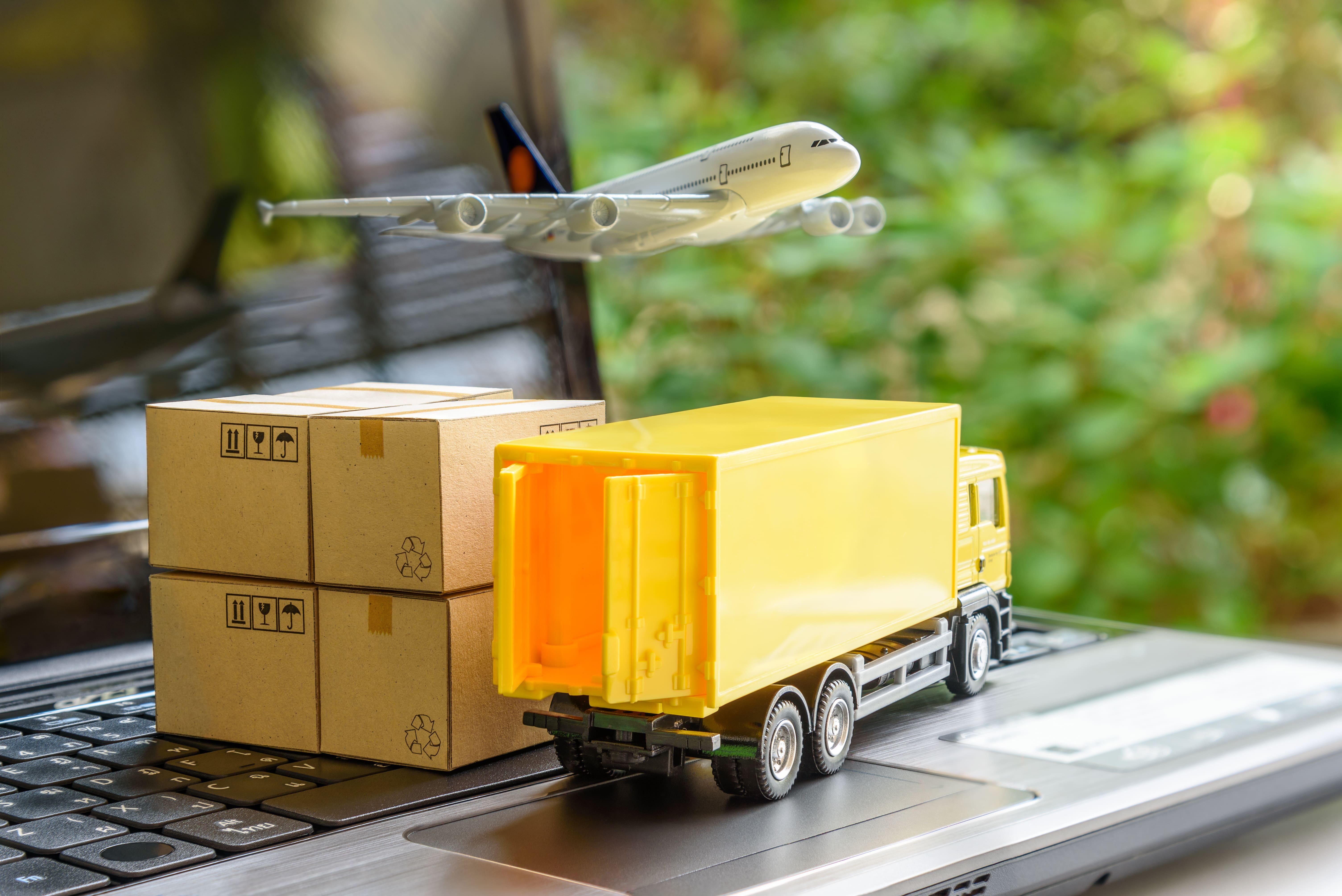 Lieferungsarten: Kleines Lieferfahrzeug, Stapel Pakete und kleines Flugzeug stehen auf der Laptop-Tastatur.