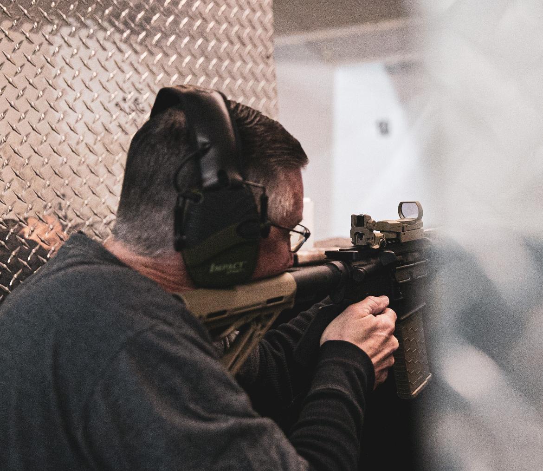 a man firing a gun at a shooting range
