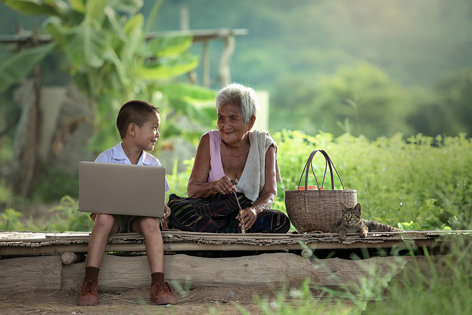 kid with a laptop sitting next to his grandmother
