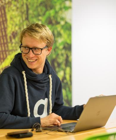 Kirill Bulatov smiling while using a computer.