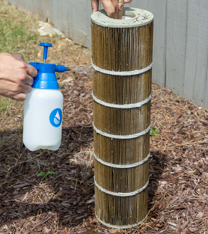 A picture showing someone spraying PreSweep cleaner onto a dirty pool cartridge filter.