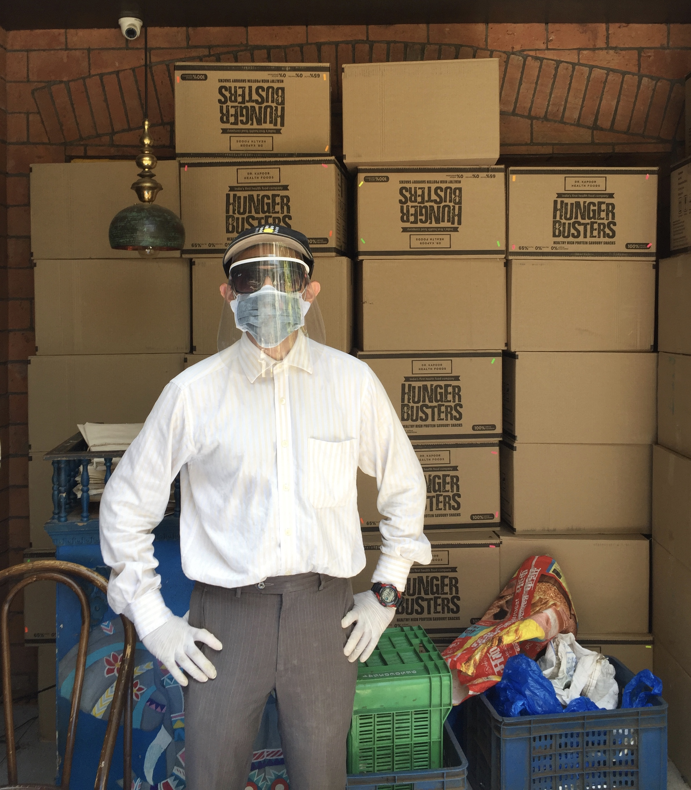 Khaana chahiye volunteer wearing a mask, standing in a warehouse