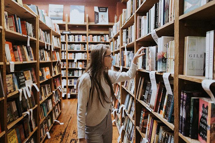 Frau greift nach Buch in Bibliothek