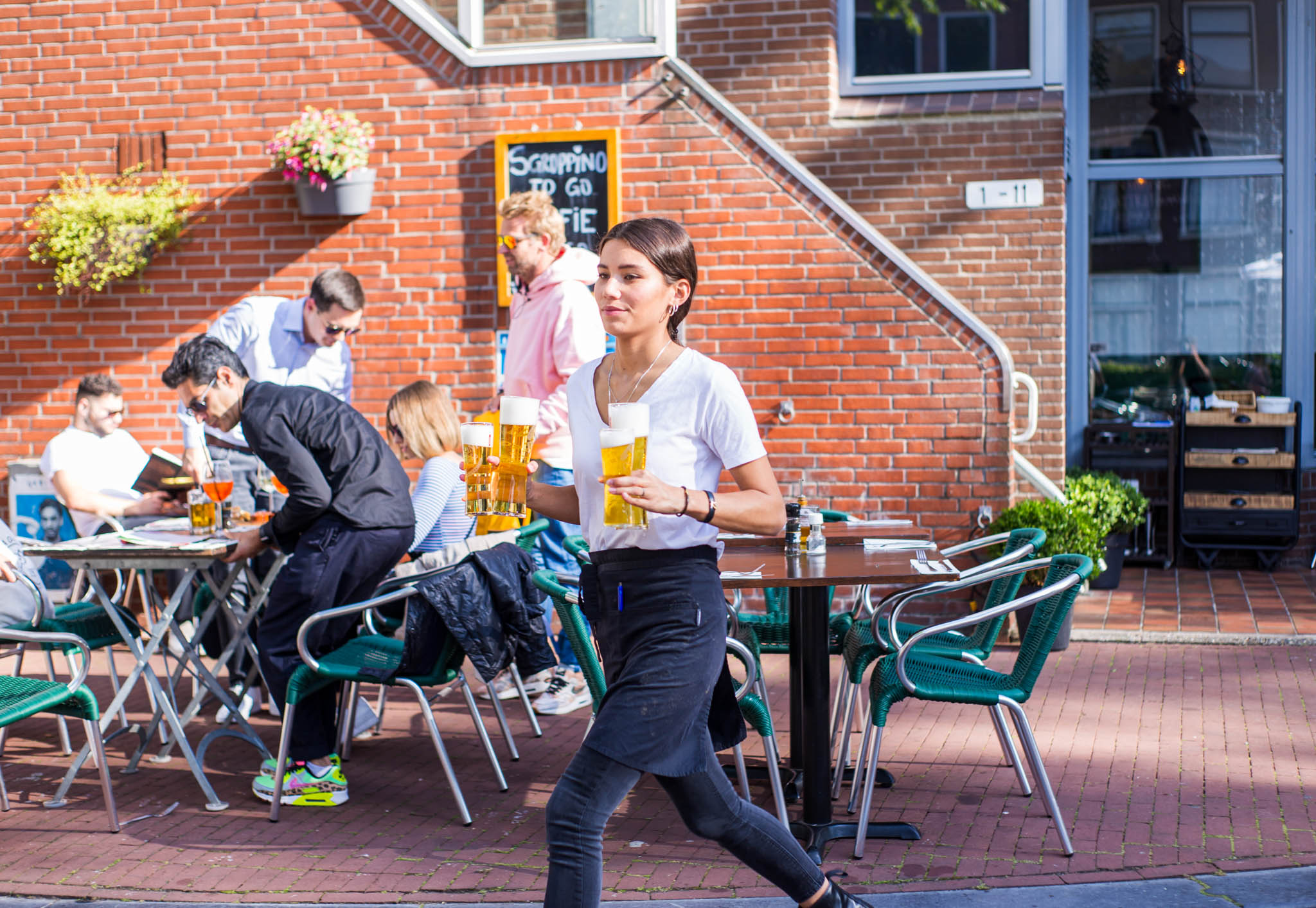 Waitress walking outside a restaurant with beer glasses