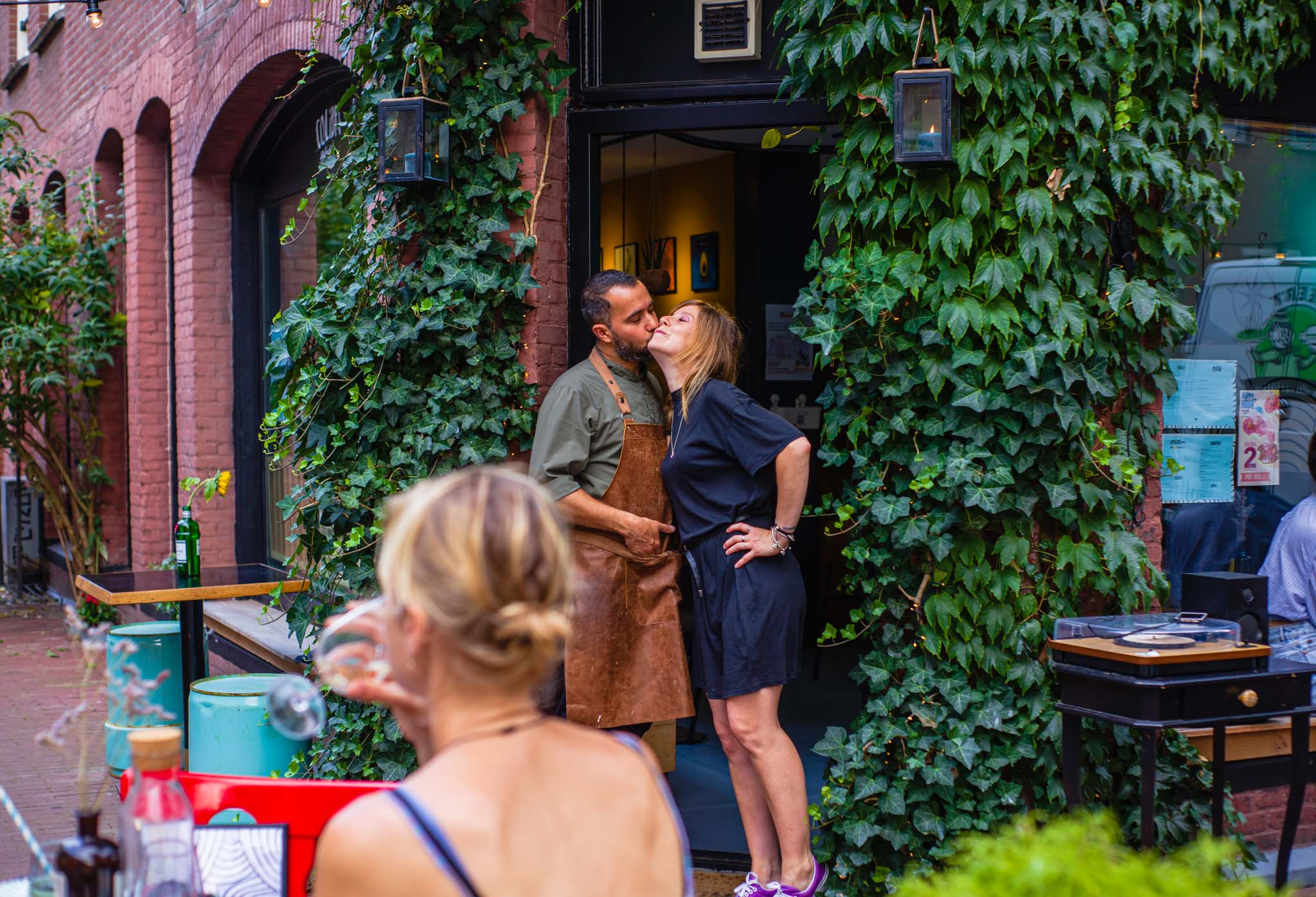 Couple kissing at the door of a restaurant