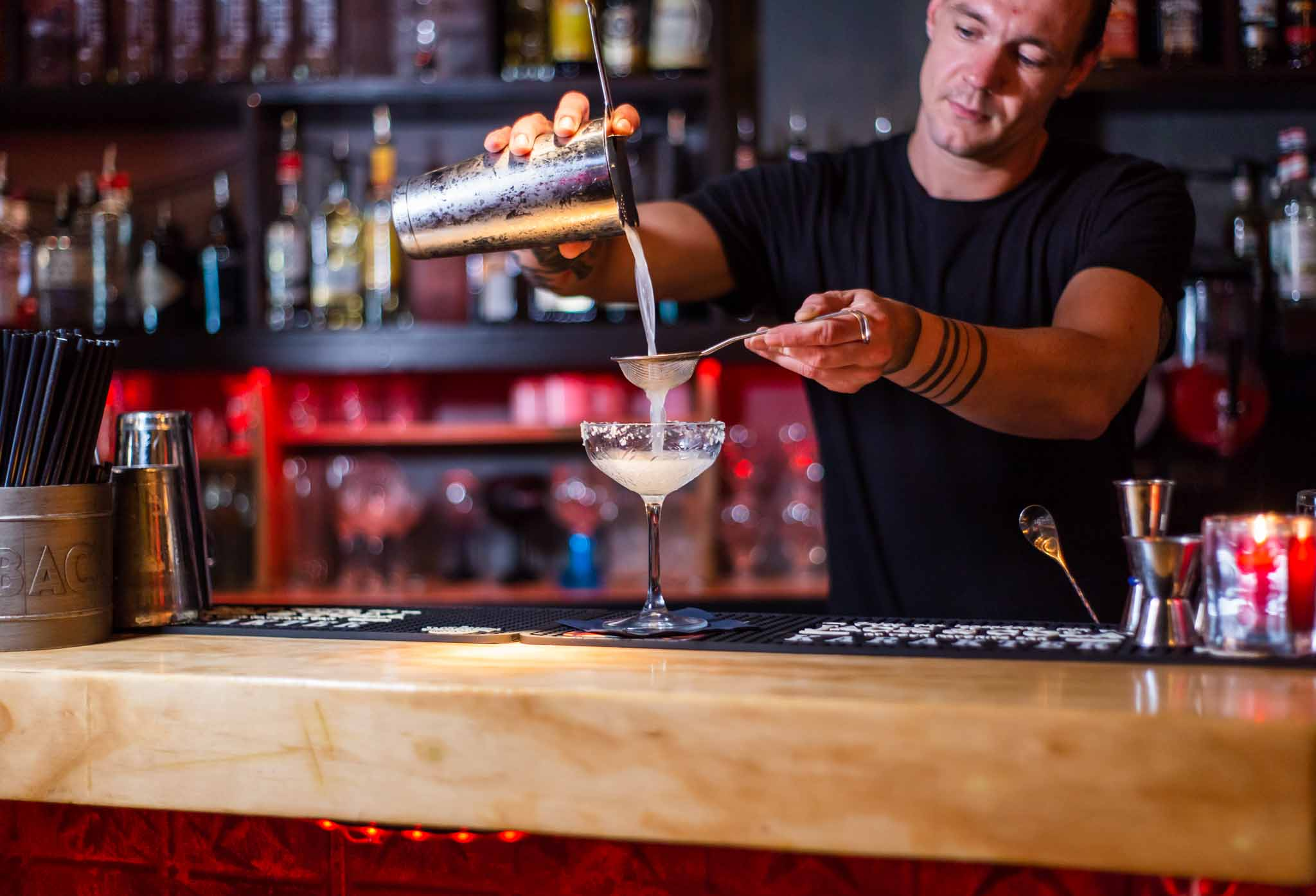 Bartender pouring cocktail into a glass in a bar