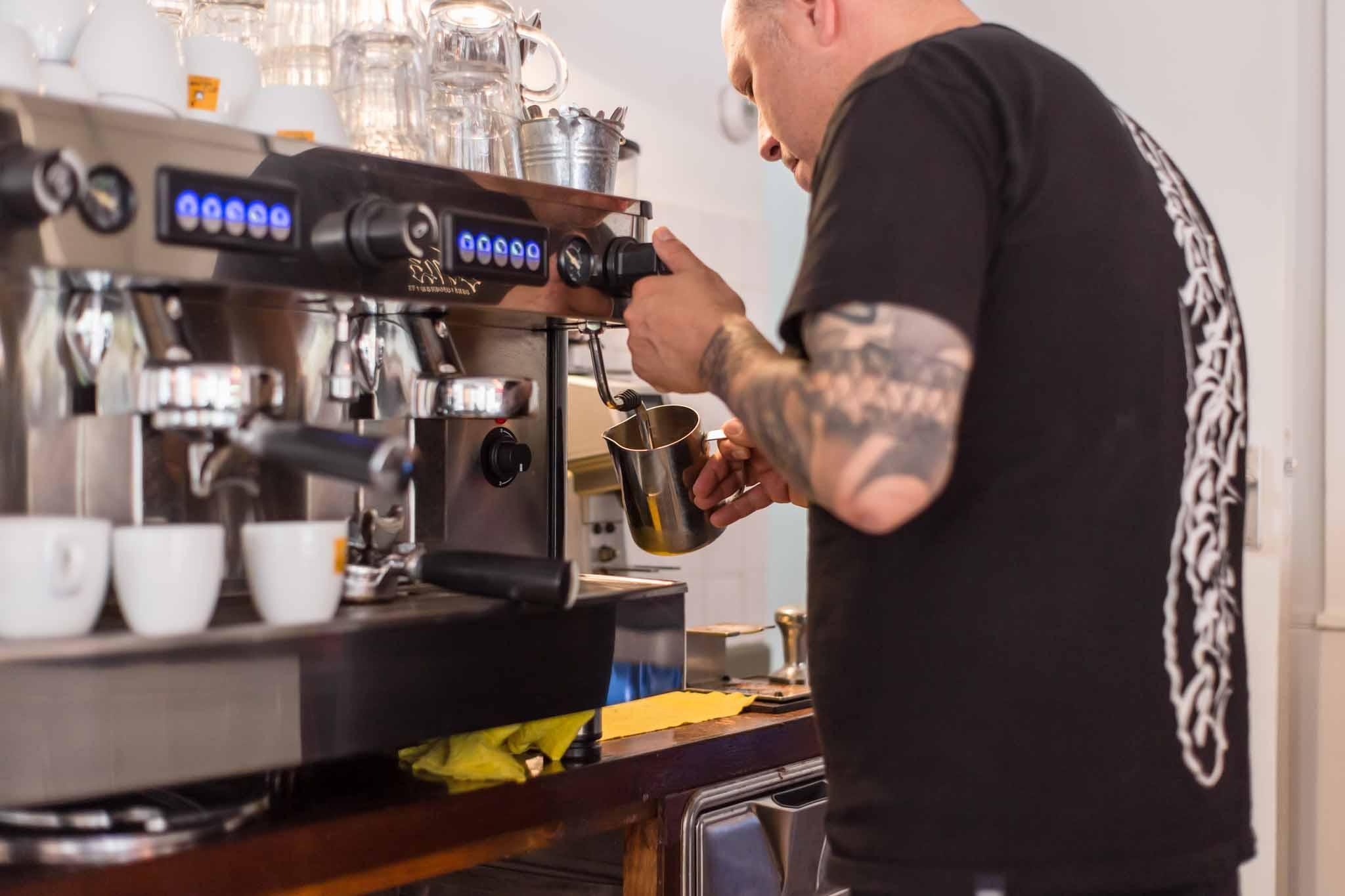 Staff in a cafe preparing coffee on a coffee machine