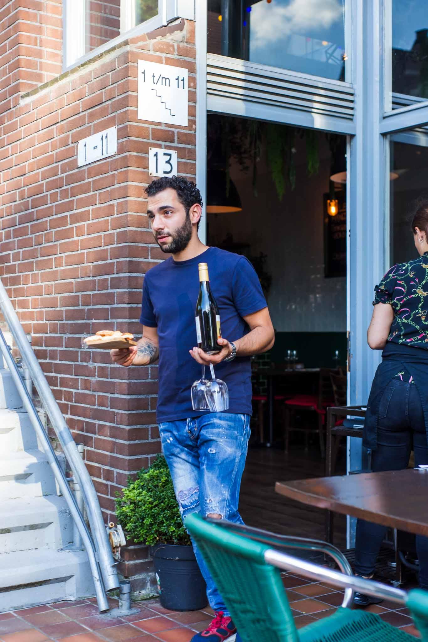 Waiter going outside an Italian restaurant to serve a dish