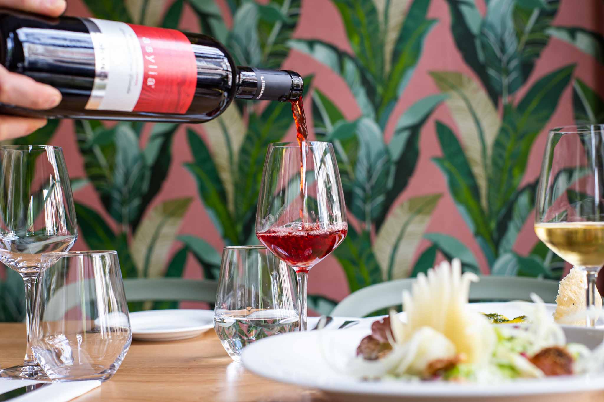 Red wine being poured into a glass in an Italian Restaurant