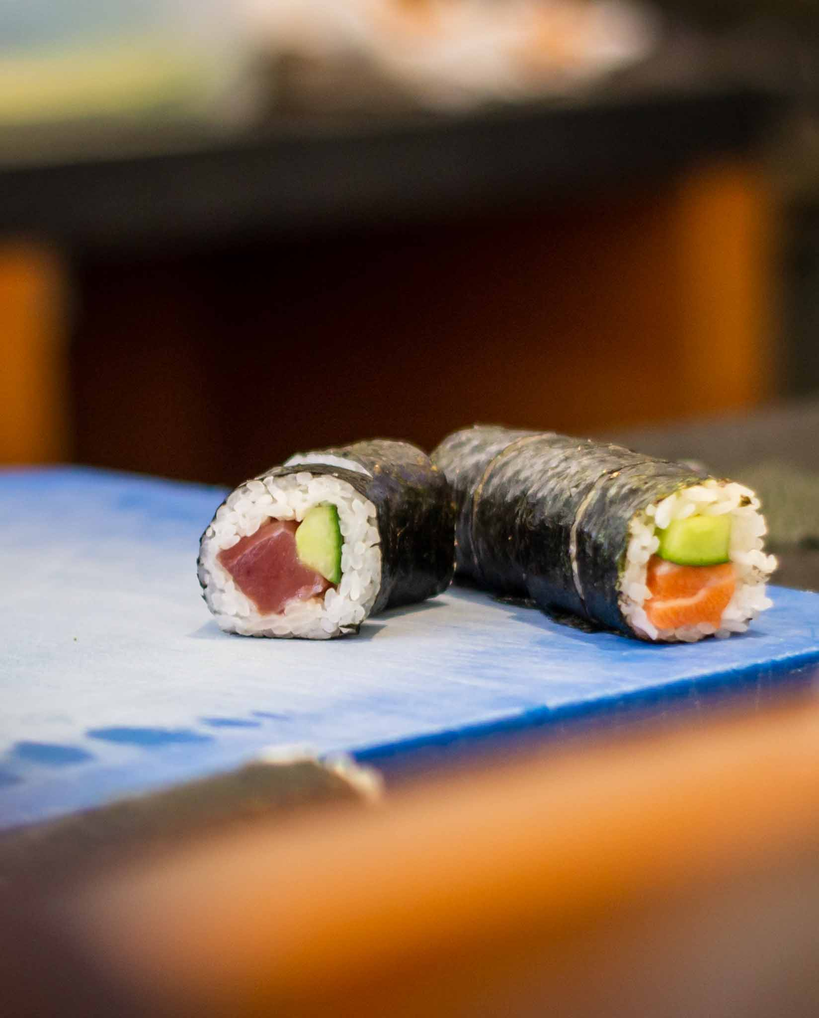 Two rolls of sushi on a blue cutting board in a Japanese restaurant