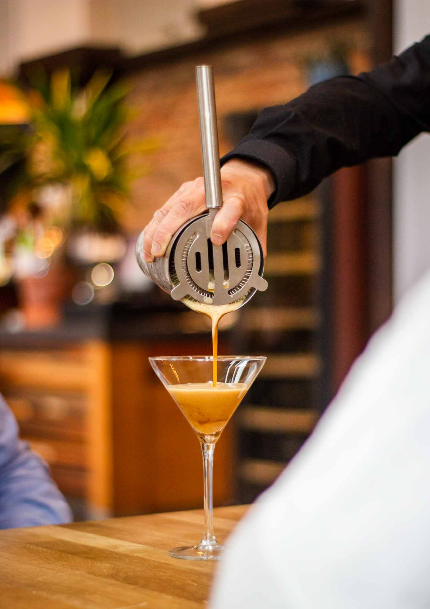 Bartender in a Mediterranean restaurant pouring cocktail