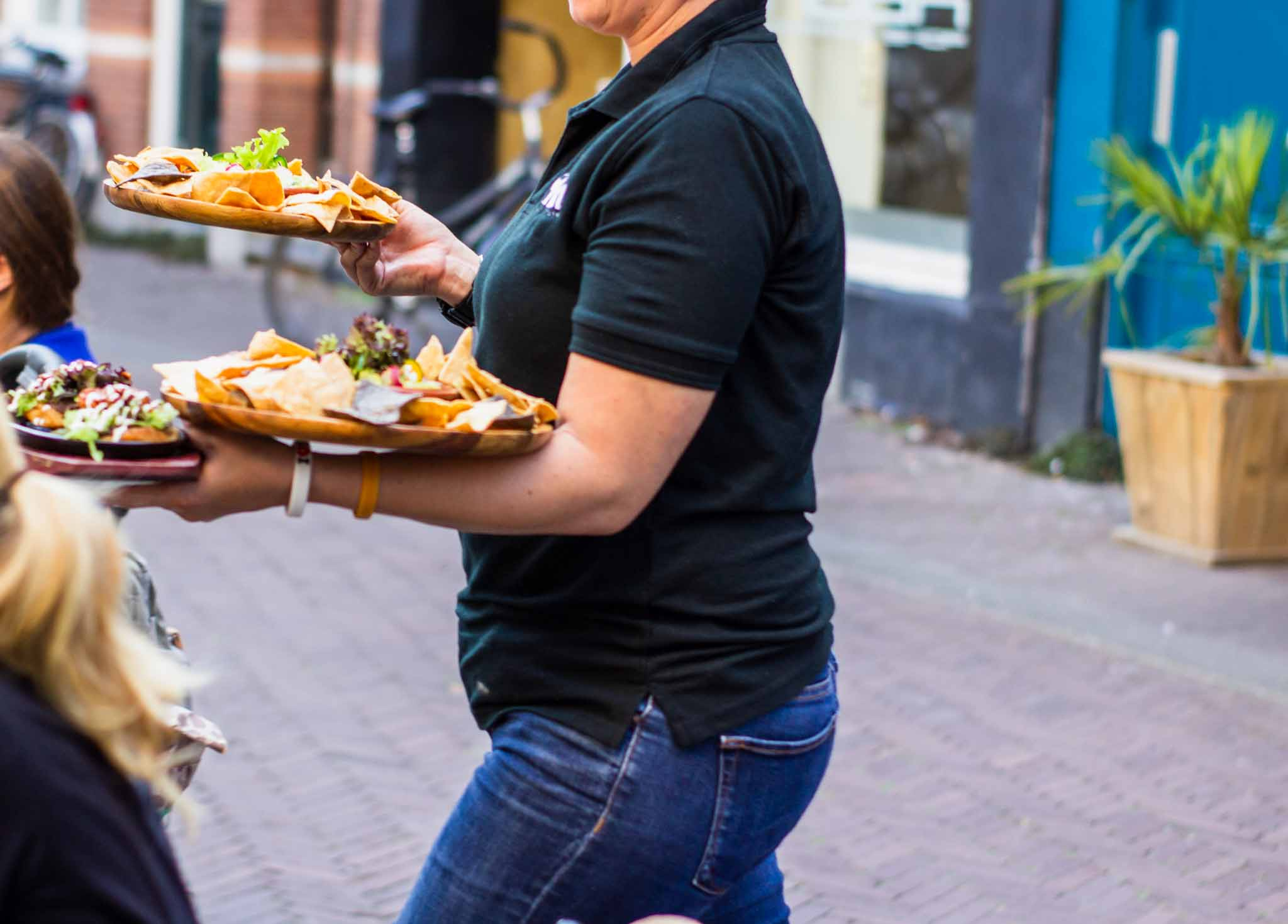 Waitress outside a Mexican restaurant serving dishes
