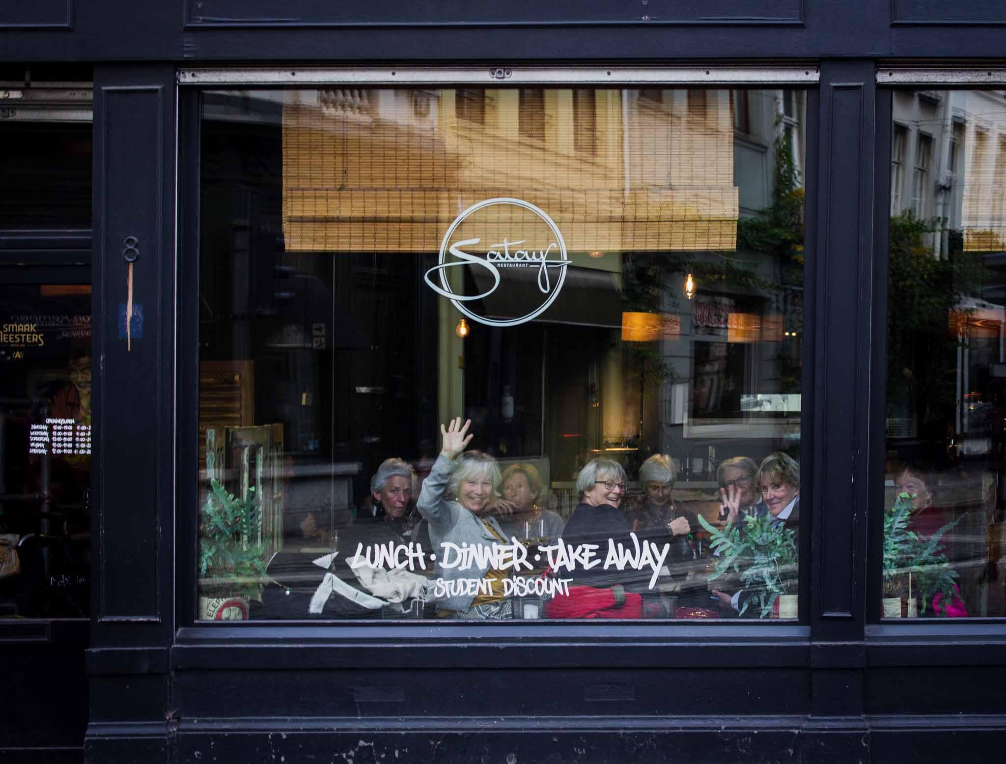 Clients in a Thai restaurant waving through the window