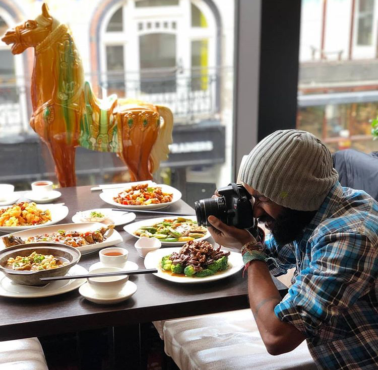 Photographer taking pictures of food in a restaurant