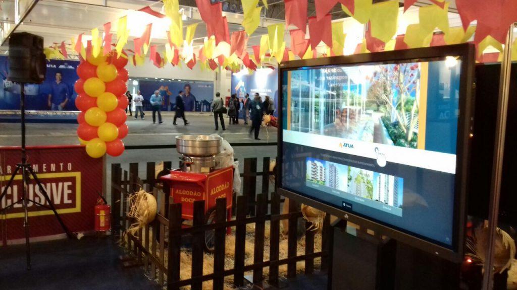Estande da Construtora Atua no Feirão da Caixa, com pipoca, bandeirolas de festa junina e Showcase Imóveis, o catálogo interativo da Aqua.