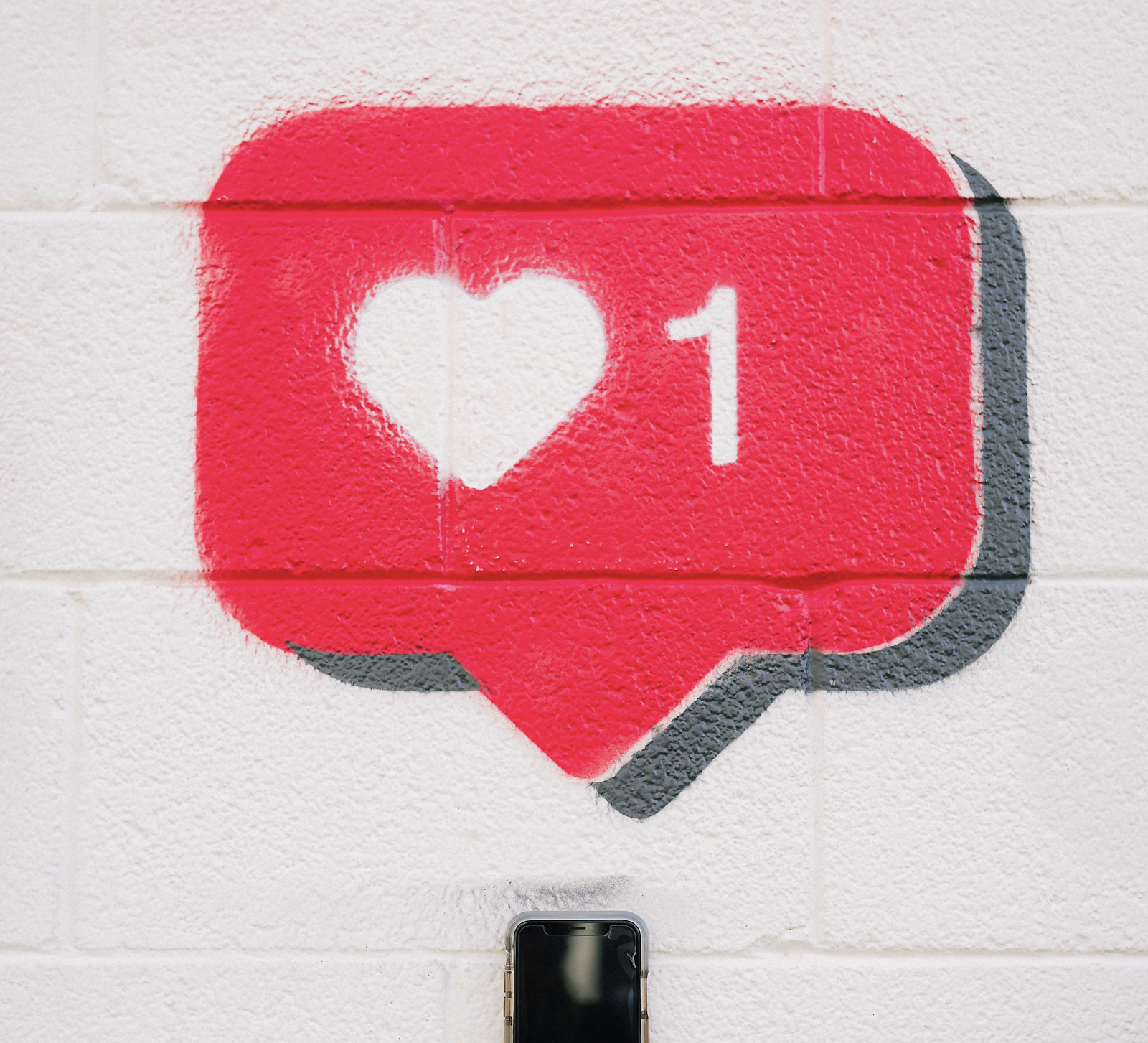 A speech bubble with a heart symbol and number 1 spray painted onto a wall above a cell phone