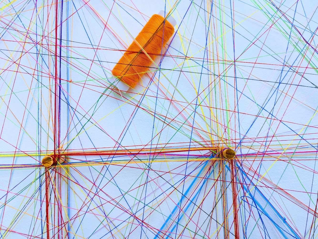 A stock image of colorful threads meeting in the middle and creating a network like effect.