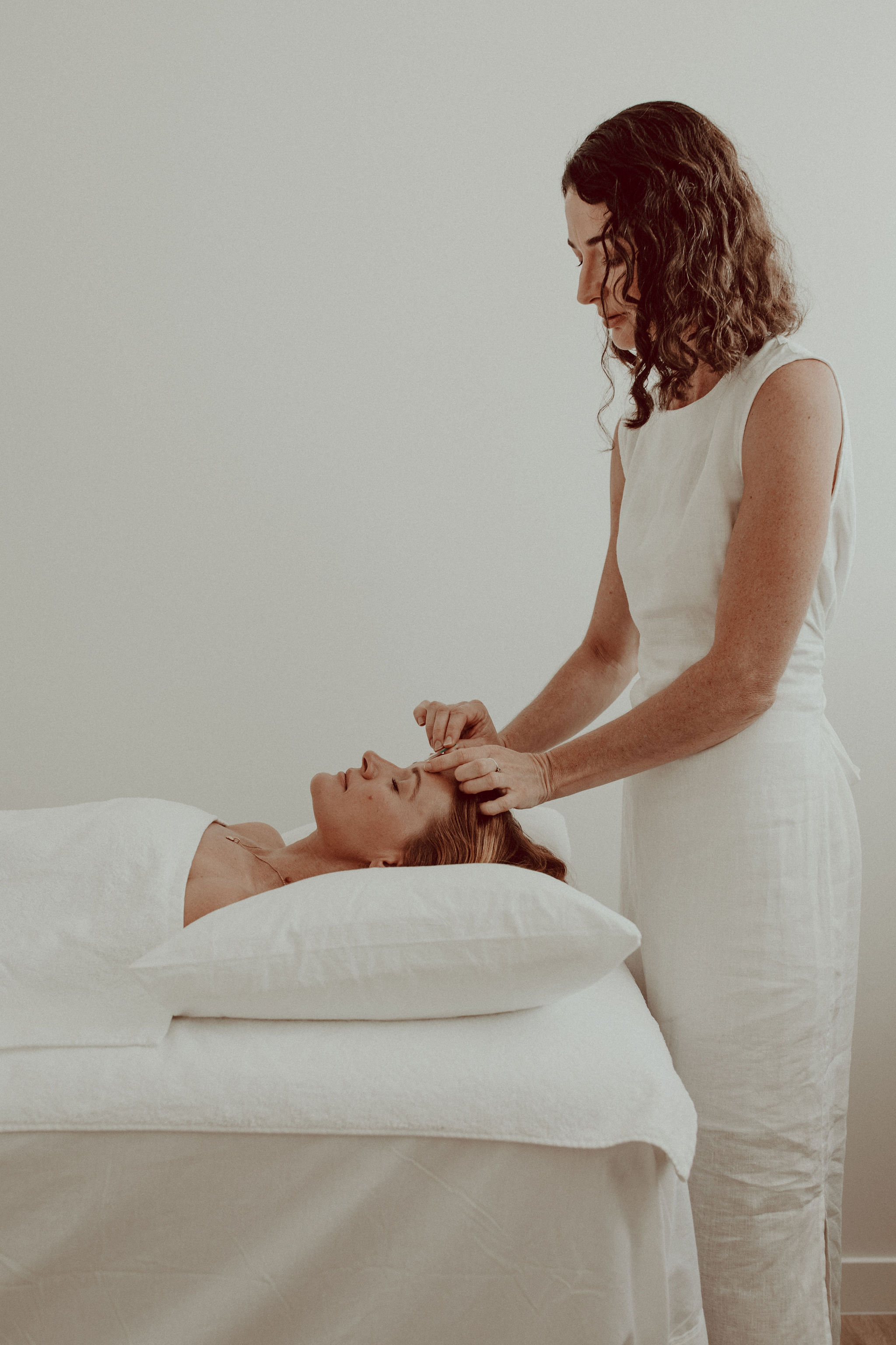 Eva Rose applying acupuncture treatment to a client
