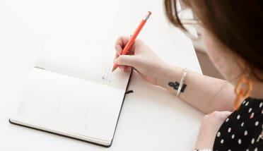 Looking over Hollie's left shoulder, she's writing in a white notebook on a white desk with an orange pen. She has a black ampersand tattoo on her wrist.
