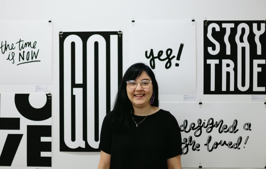 "Hollie stands in front of a gallery wall wearing a black t-shirt and black glasses. On the wall there are six of her black and white hand-lettering artworks which say, ""The time is now,"" ""love,"" ""go,"" ""yes,"" ""stay true,"" and ""she designed a life she loved."""