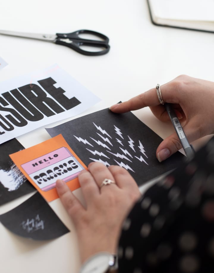 Looking over Hollie's left shoulder, Hollie's hands are arranging six pieces of paper with designs on them to create a moodboard. All of the designs are black, white, and orange. She's holding a black pen in her right hand and there is a pair of scissors on the desk.