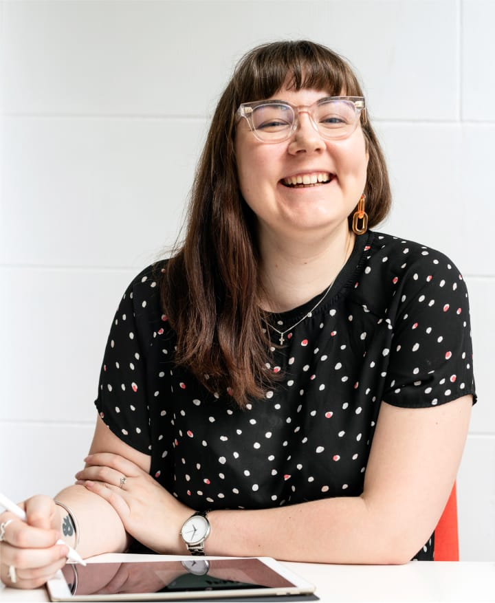 Hollie, a brand coach, sits in an orange chair at a white desk, wearing a black t-shirt with white polka-dots and clear glasses. She is holding an Apple Pencil in her right hand and smiling into the camera with an iPad on the desk.