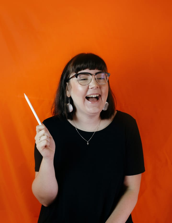 Hollie, a brand coach, is sitting in front of an orange background wearing a black t-shirt and black glasses. She is holding an Apple pencil in her right hand up in the air like a magic wand, and laughing off to the right.
