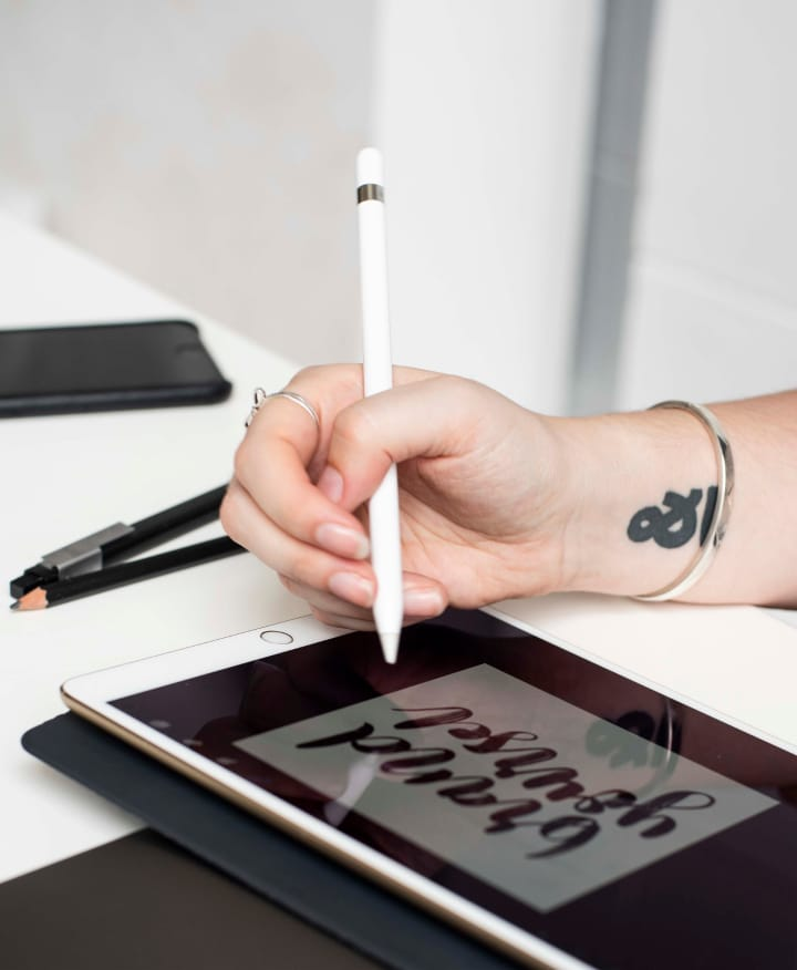 Hollie's hand is holding an Apple Pencil to draw on an iPad Pro sitting on a white desk. There is a black iPhone and two black pens on the desk too. Hollie has a black ampersand tattoo on her wrist.
