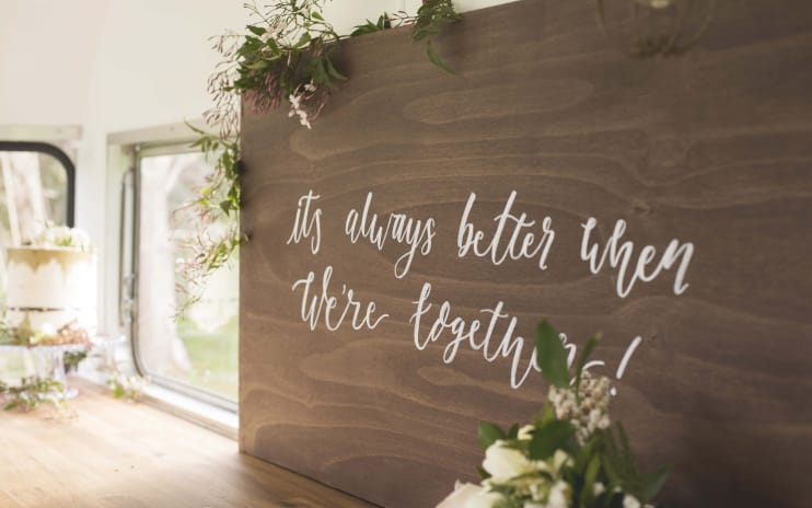 "A rectangular wooden wedding sign leaning against the window inside a white caravan with the words ""It's always better when we're together"" in white calligraphy in the centre. There is green ivy draped over the sign."