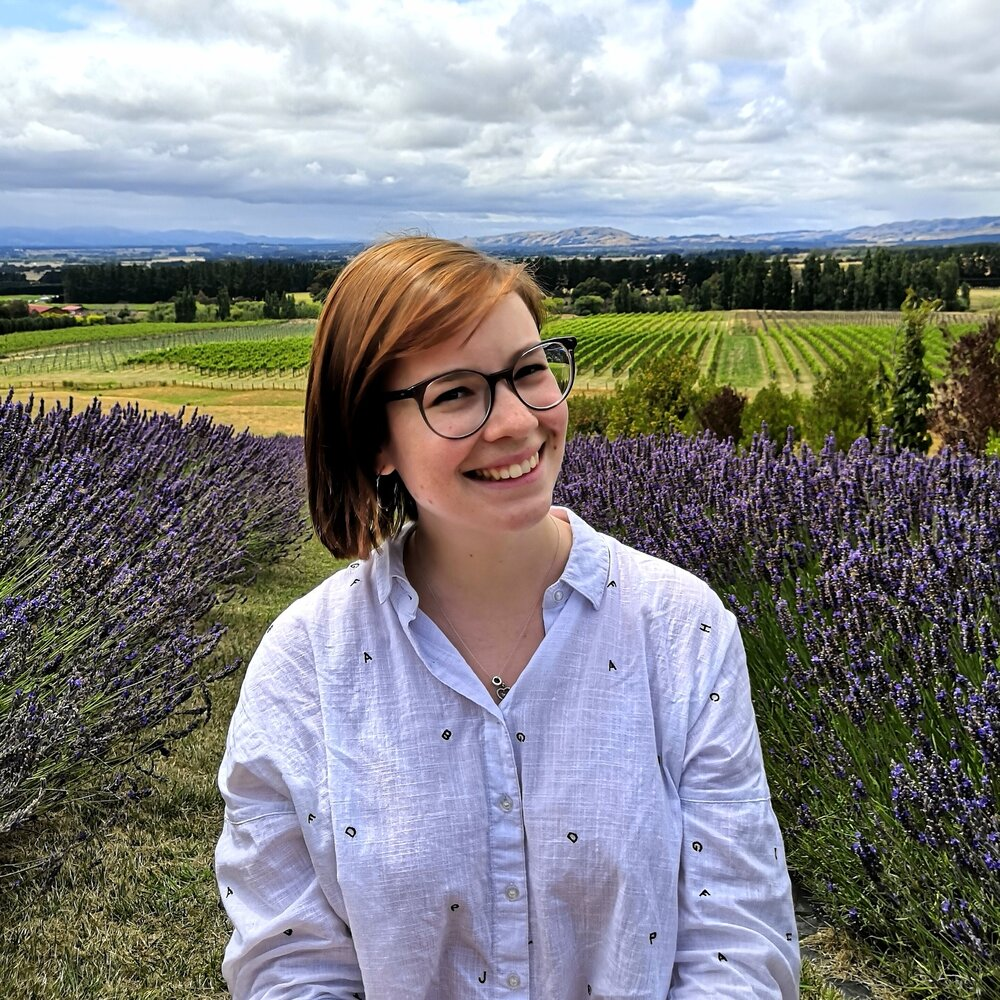 Louise, a designer, wearing a white button-down shirt and black glasses, standing in a field of lavender with her head tilted to the left and smiling into the camera.