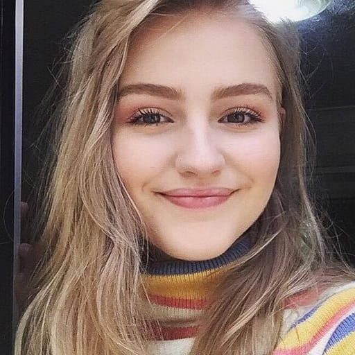 A close-up selfie of Lily, a content creator, wearing an orange and white striped turtle-neck top, smiling into the camera.