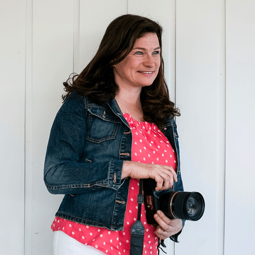 Juliet, a photographer, wearing a pink t-shirt and blue denim jacket, holding a DSLR camera and smiling off into the distance to the right, while standing in front of a white wall.
