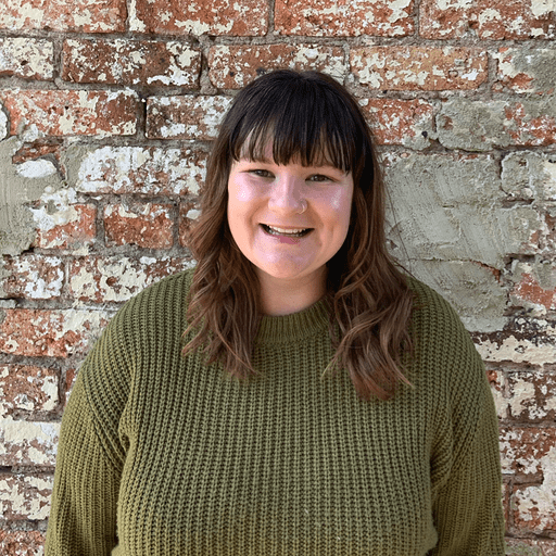 Tillie, a brand strategist, wearing a green sweater and smiling into the camera while standing against a brick wall.