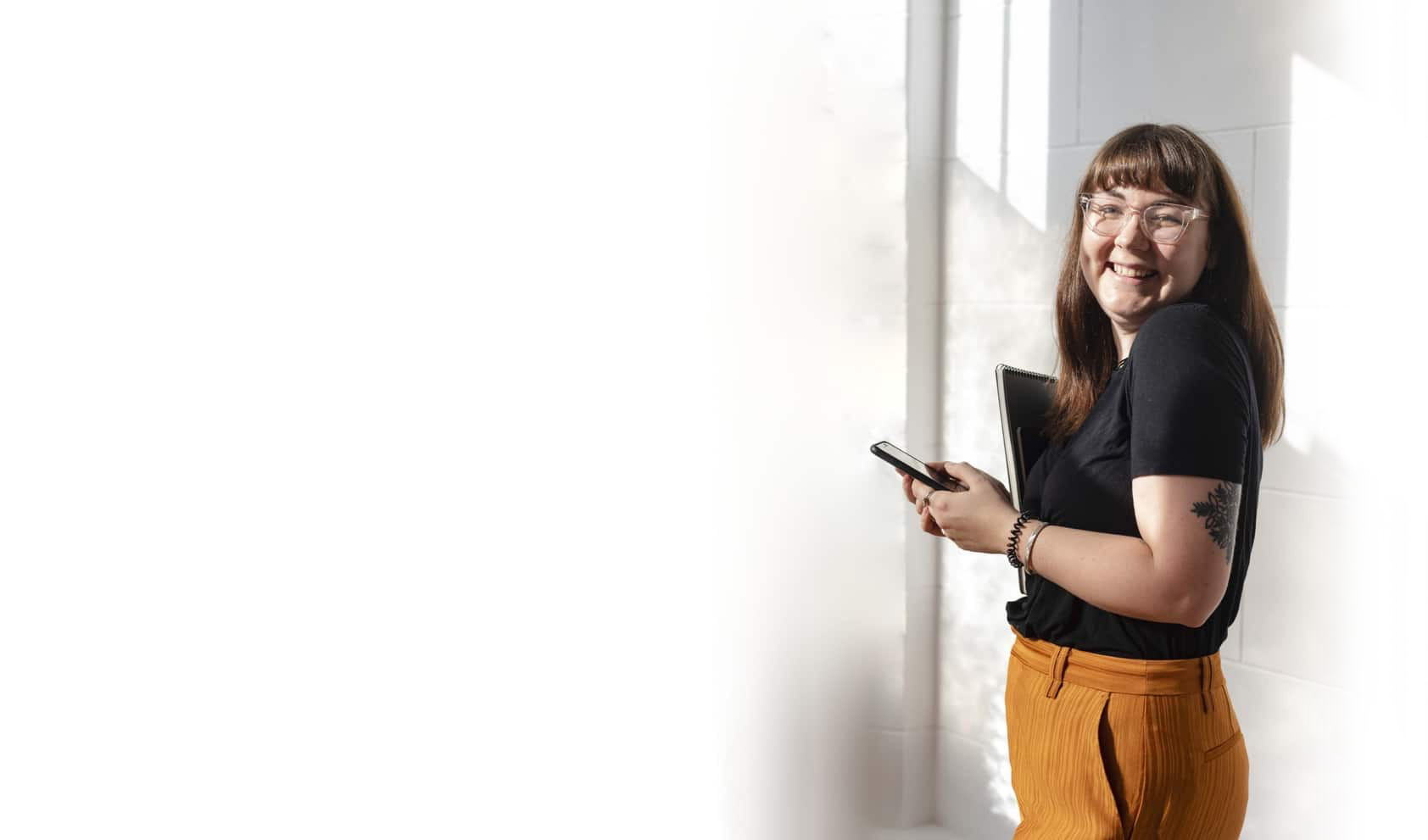 Hollie, a brand coach wearing orange pants and a black t-shirt, holding a phone and notebook, standing sideways facing left and smiling into the camera.
