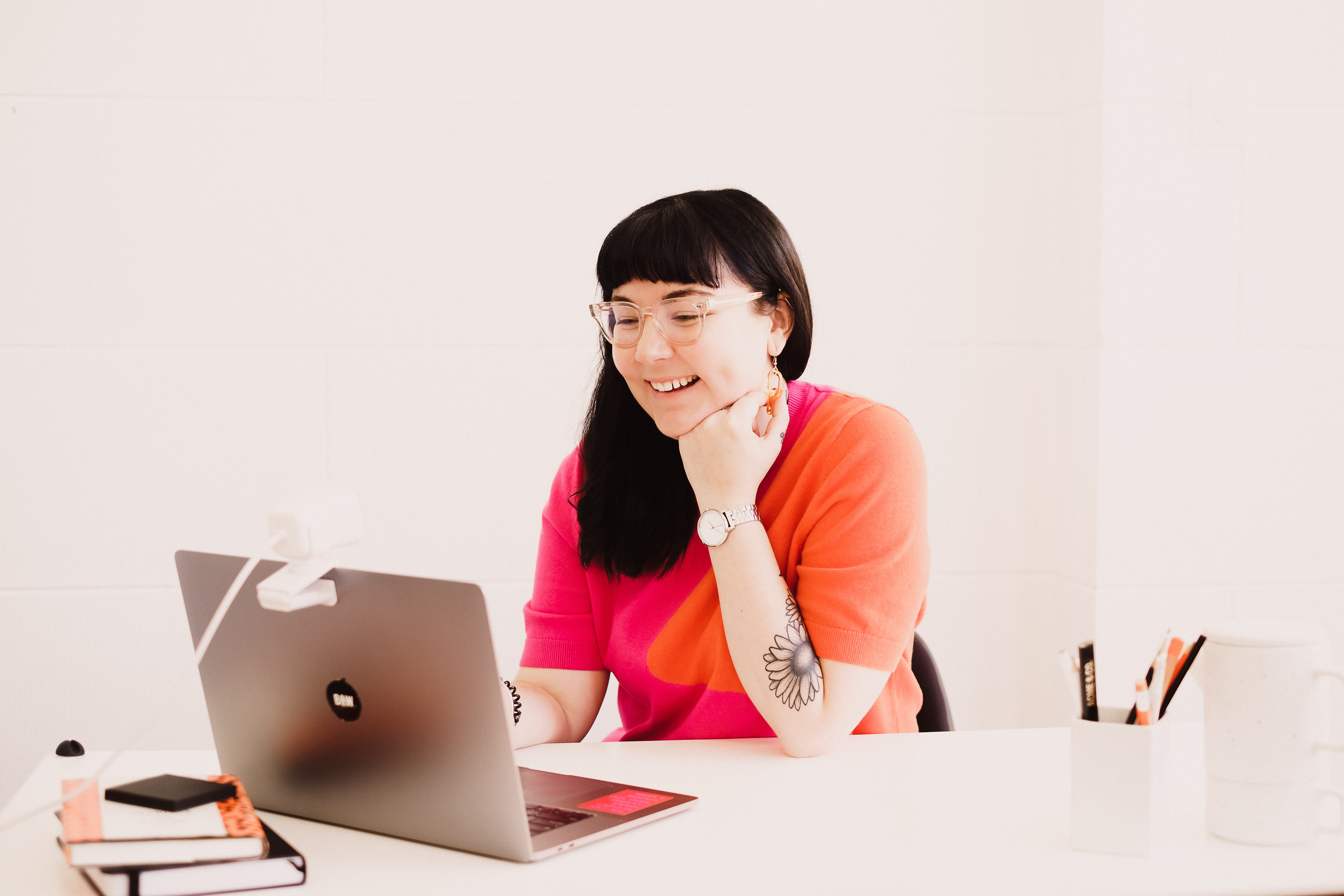 Hollie sitting behind a desk looking at a laptop, she has medium length dark hair which is down, and a full fringe. She is wearing a bright orange and pink knit sweater and is leaning on her hand.