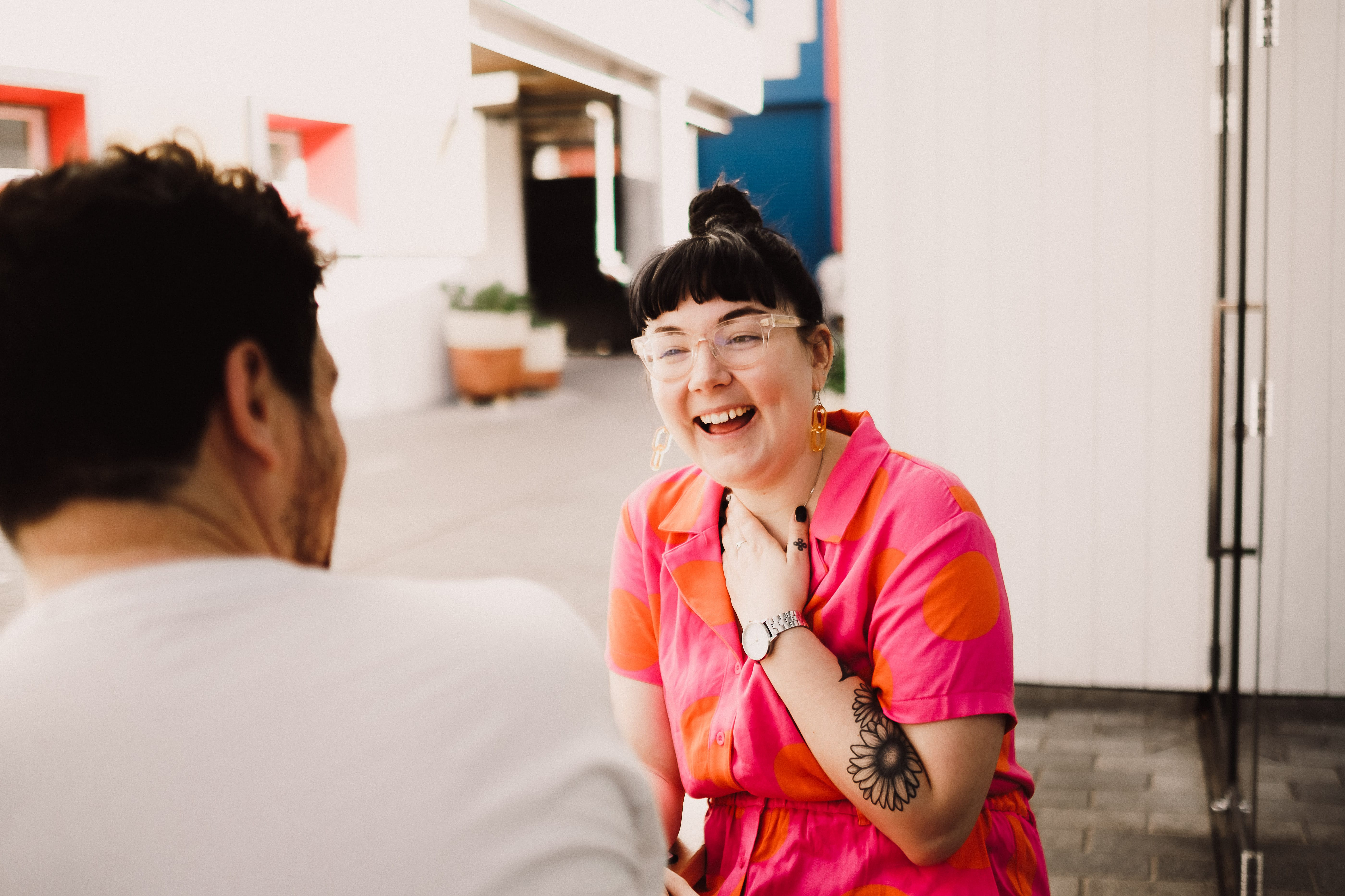 Hollie mid laugh facing the camera, sitting with a masculine looking person who looking at her out and of focus in the image. Hollie has dark hair, a full fringe and her hair up in a bun. The masculine person has on a white t'shirt and has dark hair and facial hair.