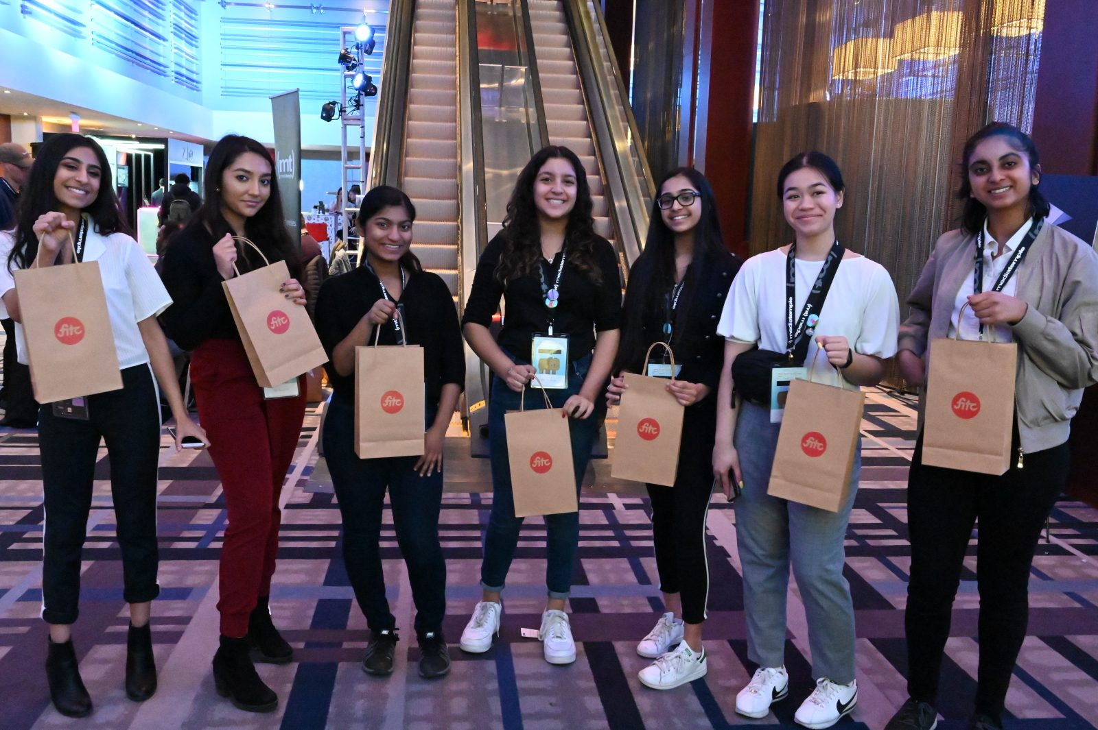 The girls at FITC 2019 showing their swag bags