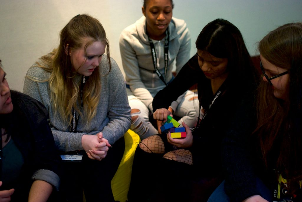A group of girls play with a Rubik's cube at FITC