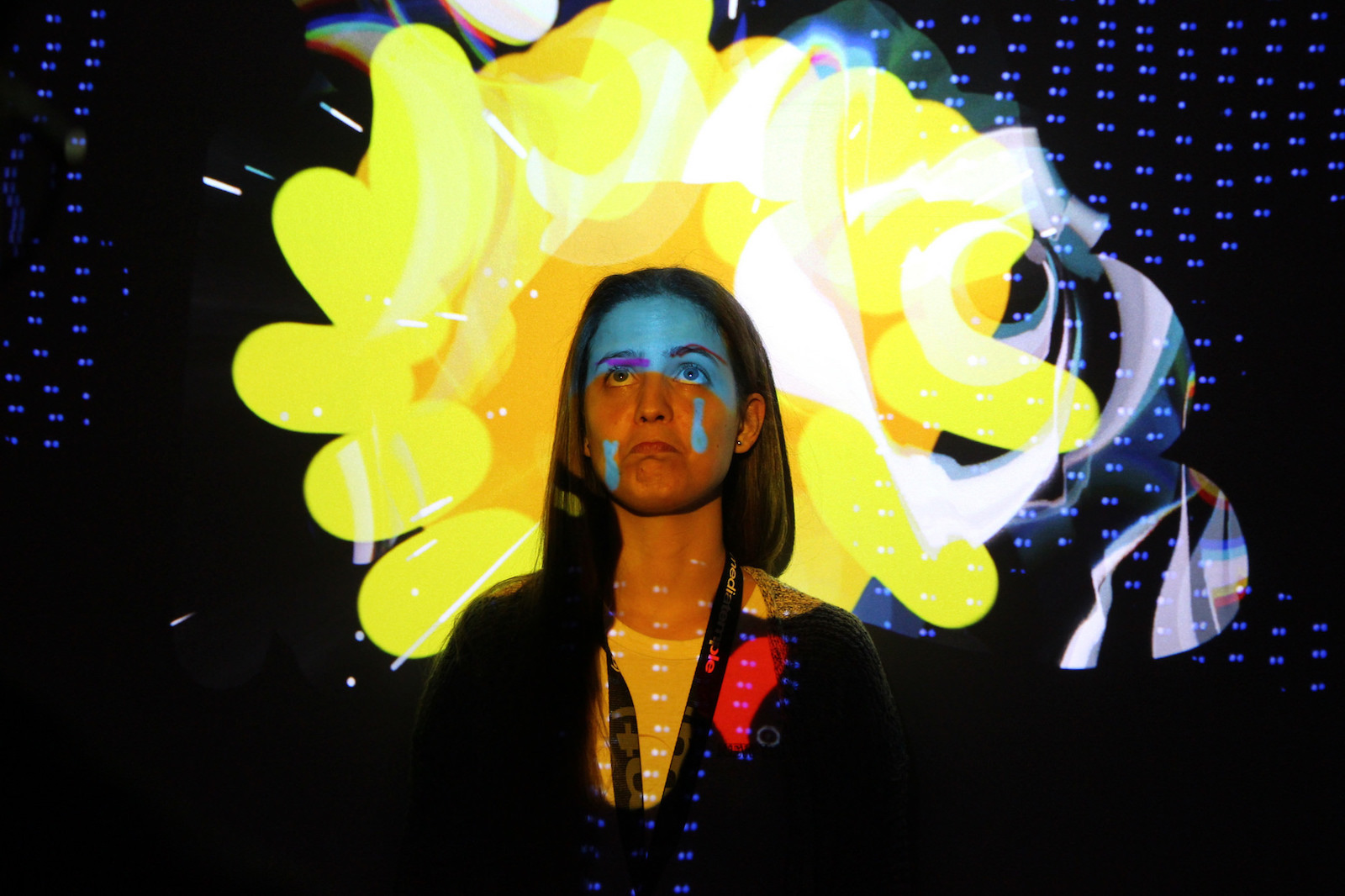 A woman stands against a digital art installation at FITC