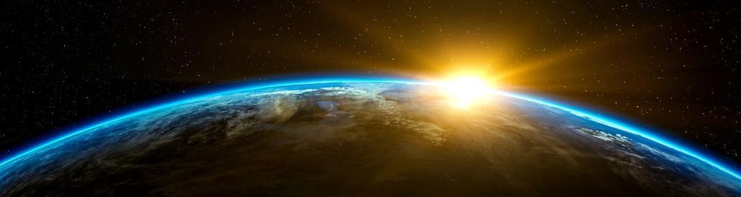 Um nascer do Sol visto do espaço, em relação ao horizonte curvilíneo do Planeta Terra.